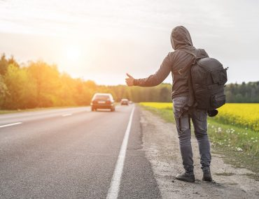 a hitchhiker catches a car on the road